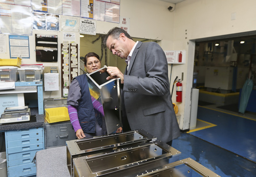In this Thursday, Oct. 10, 2013, photo, Dale Watkins Jr., President of Sheffield Platers Inc., talks with employee Eva Gasca,  at his factory in San Diego. The Commerce Department reports on orders placed with U.S. factories in November  2013 on Jan. 6, 2014. (AP Photo/Lenny Ignelzi)