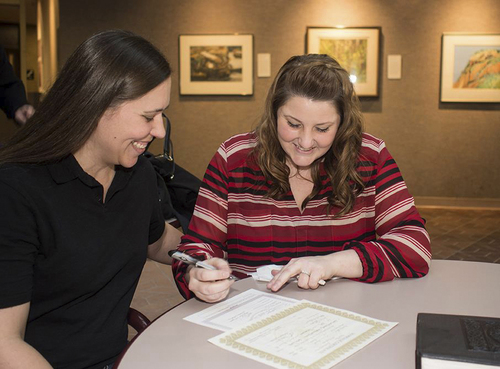 (Courtesy Coral Moser)  Misty Moser signs her marriage license at her wedding Dec. 27 in the Salt Lake County office building while her wife, Coral Moser, watches.