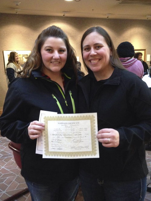 (Courtesy Coral Moser)  Misty (left) and Coral Moser pose with their marriage license at their wedding, Dec. 27, in the Salt Lake County office building.