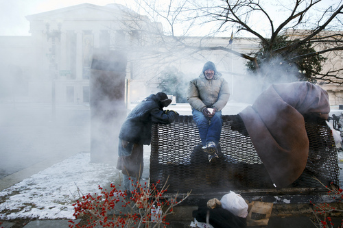 Four homeless men warm themselves on a steam grate by the Federal Trade Commission, blocks from the Capitol, during frigid temperatures in Washington, Saturday, January 4, 2014. A winter storm that swept across the Midwest this week blew through the Northeast on Friday, leaving bone-chilling cold in its wake. (AP Photo/Jacquelyn Martin)