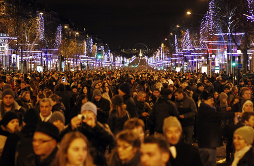 Revellers celebrate the New Year's Eve on the Champs Elysees avenue in Paris, France, Wednesday Jan. 1, 2014.(AP Photo/Remy de la Mauviniere)