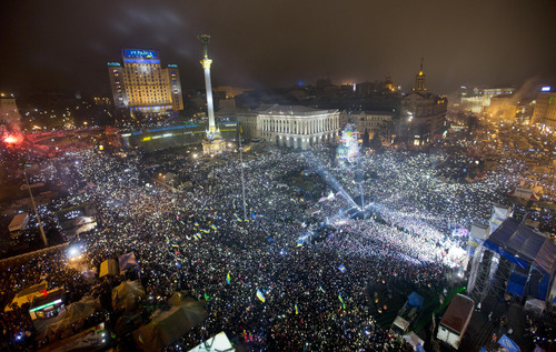 Pro-European Union activists hold light as they sing the Ukrainian national anthem, celebrating the New Year in the Ukrainian capital Kiev's main square early Wednesday, Jan. 1, 2014. At least 100,000 Ukrainians sang the country's national anthem together at the square on New Year's Eve in a sign of support for integration with Europe. Opposition leaders had called on Ukrainians to come to Kiev's Maidan on the New Year's Eve and sing the national anthem in an act of defiance and what they expected could be the record-breaking live singing of an anthem. (AP Photo/Efrem Lukatsky)