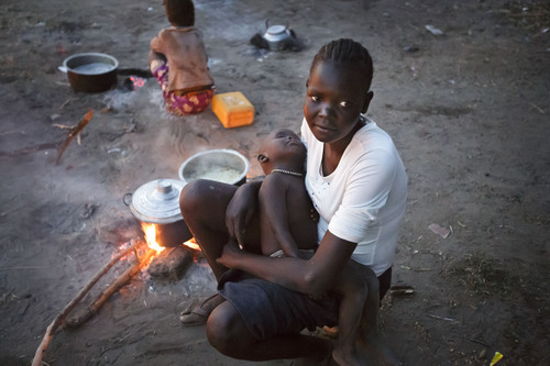 """A displaced woman and baby who fled the recent fighting between government and rebel forces in Bor by boat across the White Nile, sit by a fire as they cook food in the evening in the town of Awerial, South Sudan Wednesday, Jan. 1, 2014. The international Red Cross said Wednesday that the road from Bor to the nearby Awerial area """"is lined with thousands of people"""" waiting for boats so they could cross the Nile River and that the gathering of displaced is """"is the largest single identified concentration of displaced people in the country so far"""". (AP Photo/Ben Curtis)"""