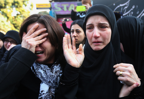 The mother of Ali Khadra, right, who was killed Thursday by a bomb explosion, mourns as she attends her son's funeral procession in the southern suburb of Beirut, Lebanon, Saturday, Jan. 4, 2014. An explosion tore through a crowded commercial street Thursday in a south Beirut neighborhood that is bastion of support for the Shiite group Hezbollah, killing several people, setting cars ablaze and sending a column of black smoke above the Beirut skyline. (AP Photo/Hussein Malla)