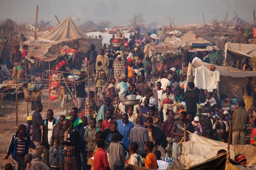 People displaced by violence walk amongst makeshift shelters in a section of a sprawling camp abutting Mpoko Airport, in Bangui, Central African Republic, Saturday, Jan. 4, 2014. According to the United Nations refugee agency, 100,000 people now live in the airport camp, and more than half the population of the capital is displaced. Insecurity has hindered distribution of food and tarps across the city, and people living at the airport have received virtually no assistance. Doctors Without Borders, who was operating several health posts within the camp, suspended all but emergency services this week amid growing insecurity.(AP Photo/Rebecca Blackwell)