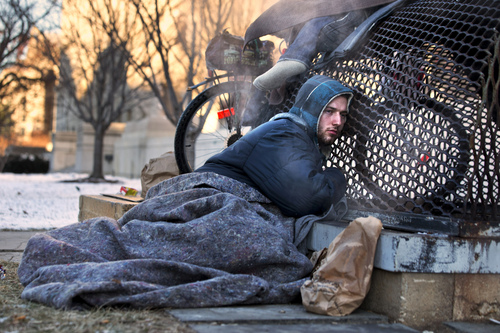Nick warms himself on a steam grate with three other homeless men by the Federal Trade Commission, just blocks from the Capitol, during frigid temperatures in Washington, Saturday, Jan. 4, 2014. A winter storm that swept across the Midwest this week blew through the Northeast on Friday, leaving bone-chilling cold in its wake. (AP Photo/Jacquelyn Martin)