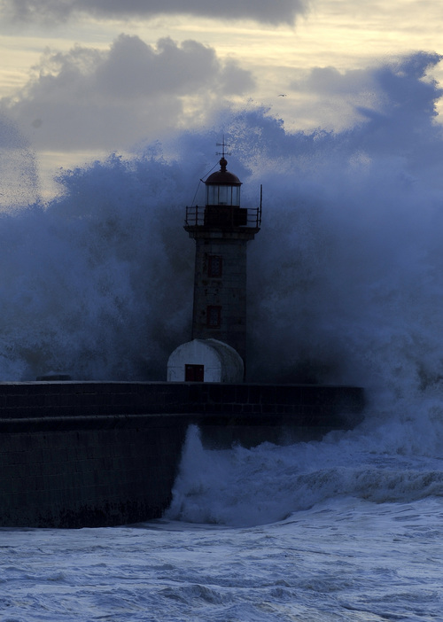Heavy seas and waves crash over a lighthouse at Douro's River mouth in Porto, Portugal, Saturday, Jan. 4, 2014. The weather forecast predicts strong winds and heavy rain for the next days, with the entire coastal area of Continental Portugal under warning due to rough seas, with the possibility of waves up to seven meters.(AP Photo/Paulo Duarte)