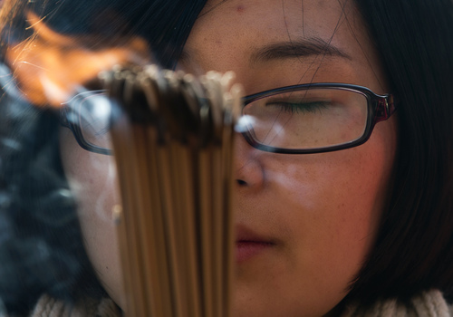 A Chinese woman prays on the first day of the New Year at the Yonghegong Lama Temple in Beijing Wednesday, Jan. 1, 2014. (AP Photo/Andy Wong)