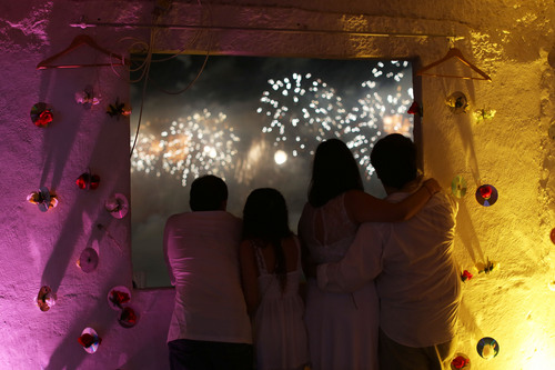 People on a rooftop in the Pavao Pavaozinho slum watch fireworks exploding over Copacabana beach during New Year's Eve celebrations in Rio de Janeiro, Brazil, Wednesday, Jan. 1, 2014. (AP Photo/Leo Correa)