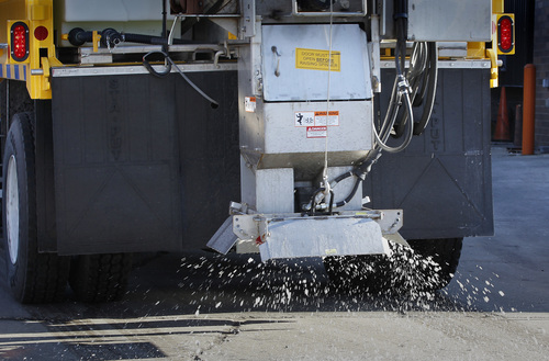 This Dec. 5, 2013 photo, cheese brine pellets are spread in the parking lot in Milwaukee.  This year Milwaukee is testing the use of cheese brine as a supplement to the use of salt on city streets. (AP Photo/Milwaukee Journal-Sentinel, Gary Porter)