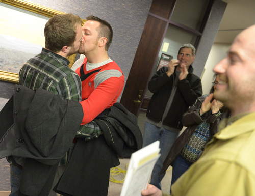 Keith Johnson | The Salt Lake Tribune  Jason Dautel, left and Micah Unice kiss after being married by officiant Derek Snarr outside the Salt Lake County clerks office, Friday, December 20, 2013. A federal judge in Utah Friday struck down the state's ban on same-sex marriage, saying the law violates the U.S. Constitution's guarantees of equal protection and due process.