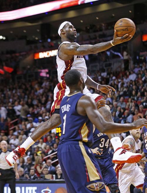 Miami Heat's LeBron James (6) drives to the basket past New Orleans Pelicans' Tyreke Evans (1) and Greg Stiemsma (34) during the second half of an NBA basketball game in Miami, Tuesday, Jan 7, 2014. The Heat defeated the Pelicans 107-88. (AP Photo/Joel Auerbach)