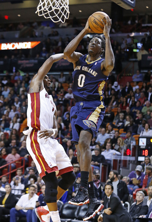New Orleans Pelicans' Al-Farouq Aminu (0) goes to the basket over Miami Heat's Chris Bosh (1) during the second half of an NBA basketball game in Miami, Tuesday, Jan 7, 2014. The Heat defeated the Pelicans 107-88. (AP Photo/Joel Auerbach)