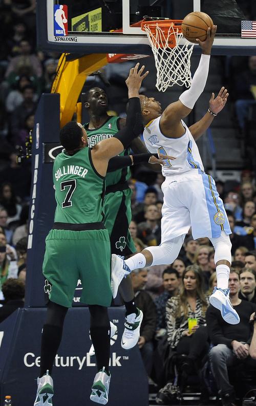 Denver Nuggets guard Randy Foye, right, scores over Boston Celtics  forward Jared Sullinger, left, and Brandon Bass, center, in the first half of an NBA basketball game on Tuesday, Jan. 7, 2014, in Denver.  (AP Photo/Chris Schneider)