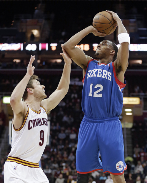Philadelphia 76ers' Evan Turner (12) shoots over Cleveland Cavaliers' Matthew Dellavedova (9), from Australia, during the second quarter of an NBA basketball game Tuesday, Jan. 7, 2014, in Cleveland. (AP Photo/Tony Dejak)