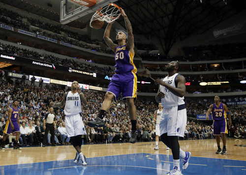 Los Angeles Lakers' Robert Sacre (50) goes up for an uncontested dunk as Dallas Mavericks' Monta Ellis (11) and DeJuan Blair, right, watch in the first half of an NBA basketball game, Tuesday, Jan. 7, 2014, in Dallas. (AP Photo/Tony Gutierrez)