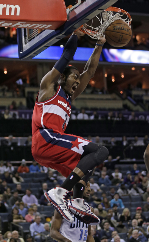 Washington Wizards' John Wall (2) dunks against the Charlotte Bobcats during the second half of an NBA basketball game in Charlotte, N.C., Tuesday, Jan. 7, 2014. The Wizards won 97-83. (AP Photo/Chuck Burton)