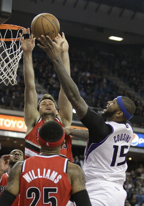 Sacramento Kings center DeMarcus Cousins, right, goes to the basket against Portland Trail Blazers center Joel Freeland, left during the third quarter of an NBA basketball game in Sacramento, Calif., Tuesday, Jan. 7, 2014.  The Kings won 123-119.(AP Photo/Rich Pedroncelli)