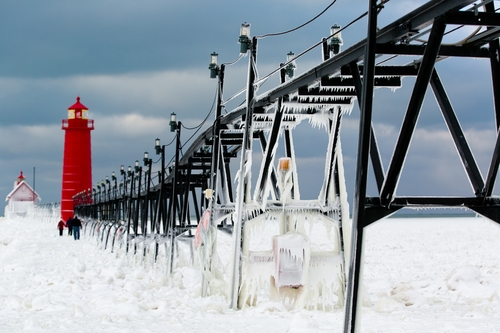 Frozen water clings to the Grand Haven South Pier on Wednesday, Jan. 8, 2014 in Grand Haven, Mich.  Cold weather lingered Thursday in Michigan as many students returned to school for the first time this year, and roads were slippery with freezing rain and snow in the forecast that could cause more problems.  (AP Photo/The Muskegon Chronicle, Natalie Kolb) ALL LOCAL TV OUT; LOCAL TV INTERNET OUT