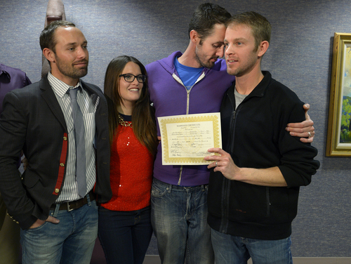 Scott Sommerdorf   |  The Salt Lake Tribune Michael Ferguson leans into his husband Seth Anderson after they were married at the Salt Lake County offices, Friday December 20, 2013. With them are friends Blake Ferguson, left, and Danielle Morgan. Michael Ferguson and Seth Anderson, (holding their marriage certificate)  were the first couple to be married under the now legal same sex marriage decision handed down by a federal judge just minutes before their ceremony.