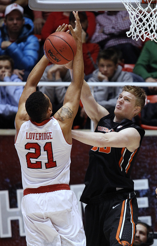 Oregon State's Olaf Schaftenaar, right, blocks the shot of Utah's Jordan Loveridge during the second half of an NCAA college basketball game in Salt Lake City, Saturday, Jan. 4, 2014. Utah beat Oregon State 80-69. (AP Photo/George Frey)
