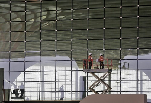 In this Wednesday, Jan. 8, 2014 photo, workers put final touches on a glass wall at the new airport terminal at the Chhatrapati Shivaji International Airport in Mumbai, India. India's overcrowded financial capital unveils its long-awaited $2 billion new airport terminal Friday, an ambitious, art-filled space that developers hope will be a showcase success in a country struggling to modernize inadequate infrastructure that is holding back economic growth. (AP Photo/Rajanish Kakade)