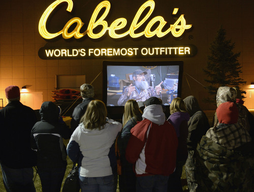 """Al Hartmann     The Salt Lake Tribune People lined up in front of Cabela's in Lehi Friday November 29 to enter the store at 5 a.m. when the doors open. Many received prizes for waiting in line.   Those towards the front of the line arrived on Thursday morning and camped out overnight.  To pass the time a giant screen shows the popular """"Duck Dynasty"""" show."""