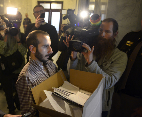 Rick Egan  | The Salt Lake Tribune    Moudi Sbeity, who with partner Derek Kitchen is a plaintiff in the lawsuit challenging Utah's ban on same-sex marriage, carries boxes with more than 58,000 signatures to the Governor's Office at the State Capitol, Friday, January 10, 2014.