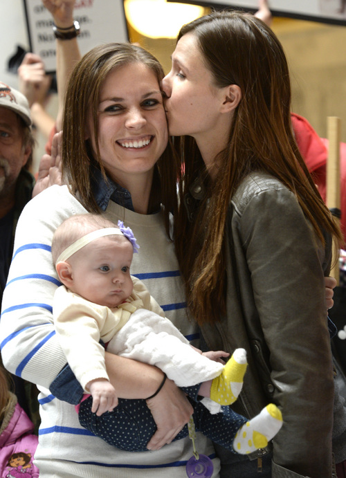Rick Egan  | The Salt Lake Tribune   Megan Berrett gets a kiss from wife Candice Berrett as she holds their daughter Quinn. The couple spoke at a rally at the State Capitol and urged Utah Gov. Gary Herbert to protect rights of families like theirs, Friday, January 10, 2014.