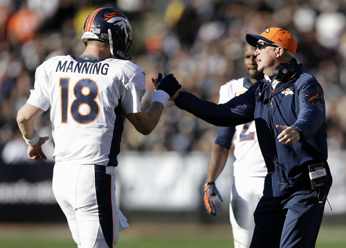 Denver Broncos quarterback Peyton Manning (18) celebrates with head coach John Fox after throwing a 63-yard touchdown pass to wide receiver Demaryius Thomas against the Oakland Raiders during the second quarter of an NFL football game in Oakland, Calif., Sunday, Dec. 29, 2013. With this score, the Broncos surpassed the 2007 New England Patriots for the most points scored in a season. (AP Photo/Marcio Jose Sanchez)