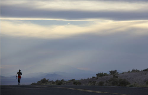 In this June 12, 2013 photo released by One Run For Boston, Thomas Hatathli carries the baton as he runs a 26-mile stage along Indian Route 15 approaching in Dilkon, Ariz., as part of a fundraising relay race to aid those injured or affected by the Boston Marathon bombings on April 15, 2013. Hundreds of runners are gearing up for another coast-to-coast fund-raising relay race, scheduled to begin March 16, 2014 in Santa Monica, Calif., and end in Boston on April 13.  (AP Photo/One Run For Boston)