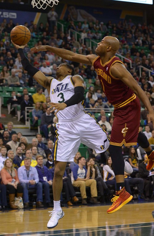 Leah Hogsten  |  The Salt Lake Tribune Utah Jazz point guard Trey Burke (3) sinks the shot and draws the foul on Cleveland Cavaliers point guard Jarrett Jack (1). The Utah Jazz leads the Cleveland Cavaliers 49-46 at the half, Friday, January 10, 2014 at Energy Solutions Arena.