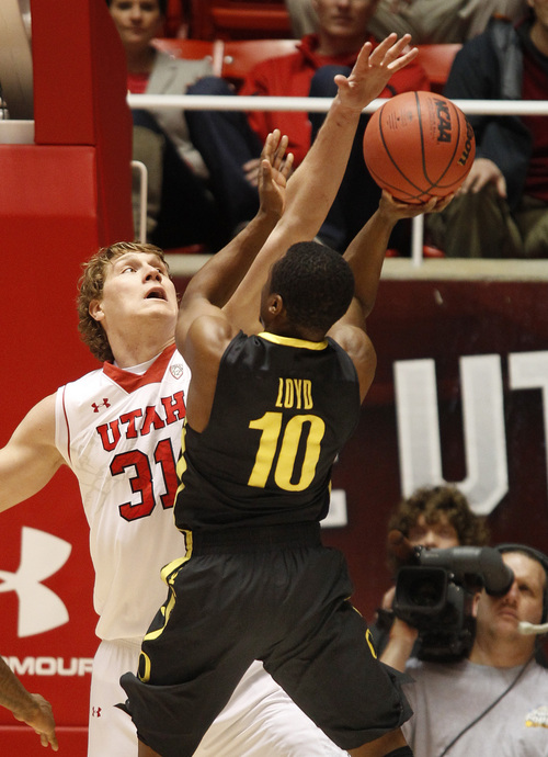 Oregon's Jonathan Lord, right, has his shot blocked by Utah's Dalon Bachynski during the first half of an NCAA college basketball game in Salt Lake City, Thursday, Jan. 2, 2014. (AP photo/George Frey)