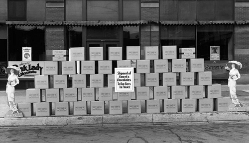 Photo Courtesy Utah State Historical Society  Image shows a stack of boxes outside the Sweet Candy factory building. The boxes are being shipped to soldiers in France in 1911.