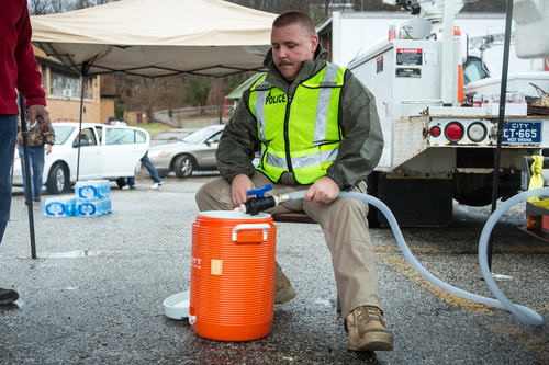 Nitro, WV Chief of Police Brian Oxley helps distribute water to local residents Saturday, Jan. 11, 2014 following the chemical spill on Thursday in Charleston, W.V. About 300,000 people in nine counties entered their third day Saturday without being able to drink, bathe in, or wash dishes or clothes with their tap water after a foaming agent escaped the Freedom Industries plant in Charleston and seeped into the Elk River.  (AP Photo Michael Switzer)