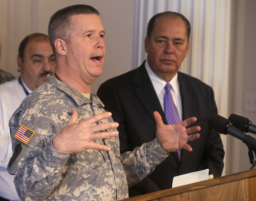 Commander of the West Virginia National Guard, Gen. James Hoyer, left, gestures as West Virginia Gov. Earl Ray Tomblin, right, looks on during a press conference at the capitol in Charleston, Va., Monday, Jan. 13, 2014 on the chemical spill that affected about 300,000 people.  The Governor announced that the water system is ready to be flushed by zones with safe drinking water.  (AP Photo/Steve Helber)