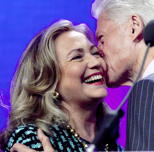 United States Secretary of State Hillary Rodham Clinton is kissed by her husband, former U.S. President Bill Clinton, as he welcomes her to  the podium at the Clinton Global Initiative, Monday, Sept. 24, 2012 in New York. (AP Photo/Mark Lennihan)