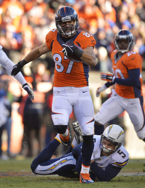 Denver Broncos wide receiver Eric Decker (87) slips away from San Diego Chargers punter Mike Scifres (5) on a return in the second quarter of an NFL AFC division playoff football game, Sunday, Jan. 12, 2014, in Denver. Scifres was injured on the play. (AP Photo/Jack Dempsey)