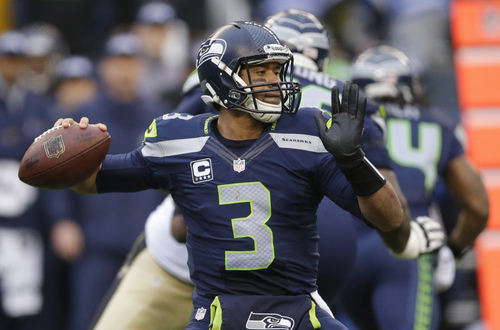 Seattle Seahawks quarterback Russell Wilson passes against the New Orleans Saints during the first half of an NFC divisional playoff NFL football game in Seattle, Saturday, Jan. 11, 2014. (AP Photo/Ted S. Warren)