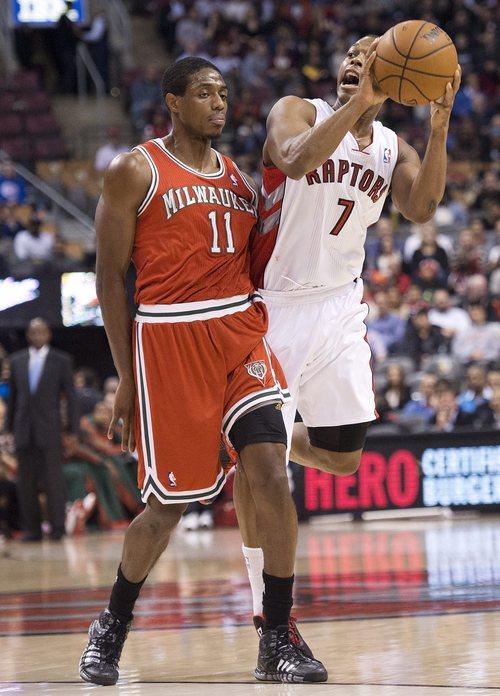 Toronto Raptors guard Kyle Lowry (7) looks to pass against Milwaukee Bucks guard Brandon Knight, left, during first half NBA basketball game in Toronto, Monday, Jan. 13, 2014.  (AP Photo/The Canadian Press, Nathan Denette)