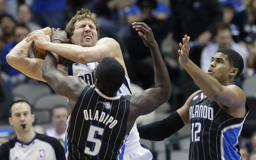 Dallas Mavericks power forward Dirk Nowitzki (41), of Germany, is fouled by Orlando Magic shooting guard Victor Oladipo (5) as Tobias Harris (12) looks on during the first half of an NBA basketball game, Monday, Jan. 13, 2014, in Dallas. (AP Photo/LM Otero)