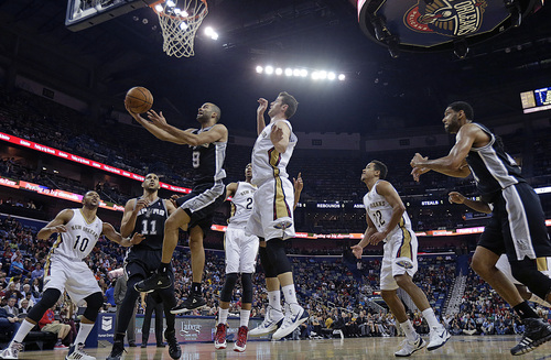 San Antonio Spurs point guard Tony Parker (9) goes to the basket against New Orleans Pelicans shooting guard Eric Gordon (10), power forward Anthony Davis, center Jason Smith and point guard Brian Roberts (22) in the first half of an NBA basketball game in New Orleans, Monday, Jan. 13, 2014. (AP Photo/Gerald Herbert)