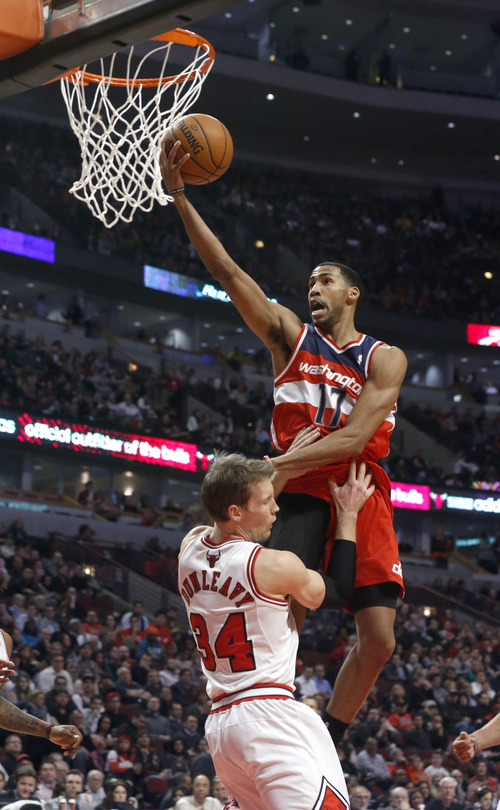 Washington Wizards guard Garrett Temple (17) scores over Chicago Bulls forward Mike Dunleavy (34) during the first half of an NBA basketball game, Monday, Jan. 13, 2014, in Chicago. (AP Photo/Charles Rex Arbogast)