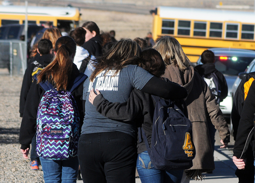 Students are escorted from Berrendo Middle School after a shooting incident, Tuesday, Jan. 14, 2014, in Roswell, N.M. Roswell police said the suspected shooter was arrested at the school, but authorities have not said if there were any injuries. The school has been placed on lockdown. No other details are yet available. (AP Photo/Roswell Daily Record, Mark Wilson)