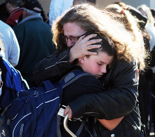 A woman hugs a student at a staging ground set up at the Roswell Mall following a shooting at Berrendo Middle School, Tuesday, Jan. 14, 2014, in Roswell, N.M. A shooter opened fire at the middle school, injuring at least two students before being taken into custody. Roswell police said the school was placed on lockdown, and the suspected shooter was arrested. (AP Photo/Roswell Daily Record, Mark Wilson)