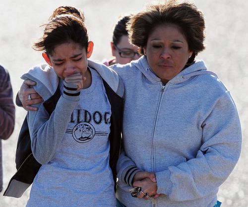 A student, left, is hugged after being united with families following a shooting at Berrendo Middle School, Tuesday, Jan.14, 2014, in Roswell, N.M. A shooter opened fire at the middle school, injuring at least two students before being taken into custody. Roswell police said the school was placed on lockdown, and the suspected shooter was arrested. (AP Photo/Roswell Daily Record, Mark Wilson)
