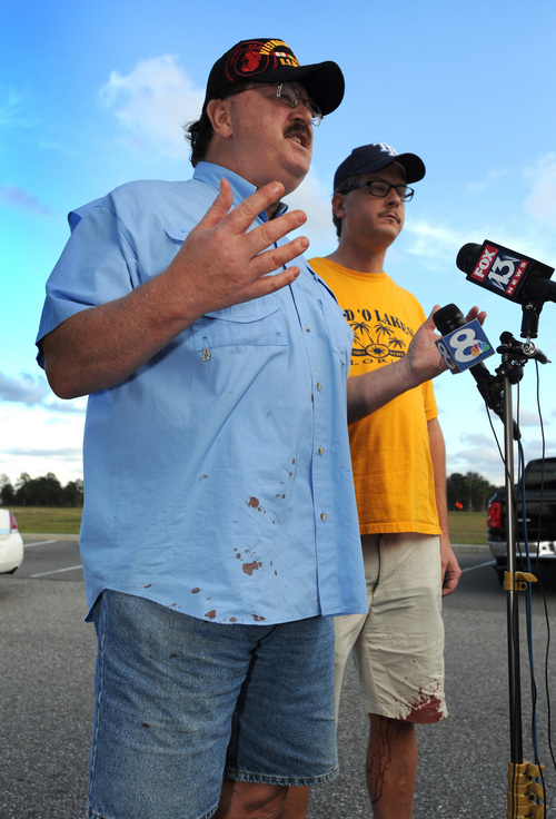 Charles Cummings, left, and Alex Cummings talk to media after witnessing a shooting inside Cobb theater Monday, Jan 13, 2014, in Wesley Chapel, Fla. Authorities say a retired Tampa police officer has been charged with fatally shooting a man during an argument over cellphone use at the theater. (AP Photo/The Tampa Tribune, Cliff Mcbride)
