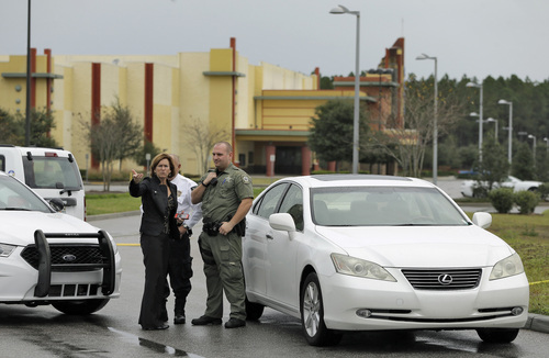 Property manager Helen Ciesla, left, gestures as she talks to a Pasco County sheriff's deputy outside the driveway to the Cobb theater Tuesday, Jan. 14, 2014, in Wesley Chapel , Fla. A 71-year old retired Tampa, Fla., police officer is charged with second degree murder after shooting Chad Oulson during a cell phone dispute inside the theater.  Oulson's wife Nicole was also shot while trying to protect her husband. (AP Photo/Chris O'Meara)