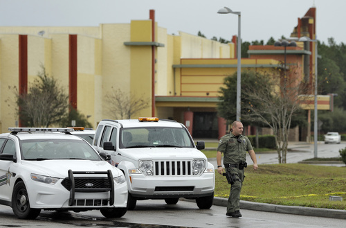 A Pasco County sheriff's deputy stands guard outside the driveway to the Cobb theater Tuesday, Jan. 14, 2014, in Wesley Chapel , Fla. A 71-year old retired Tampa, Fla., police officer is charged with second degree murder after shooting Chad Oulson during a cell phone dispute inside the theater.  Oulson's wife Nicole, was also shot while trying to protect her husband. (AP Photo/Chris O'Meara)