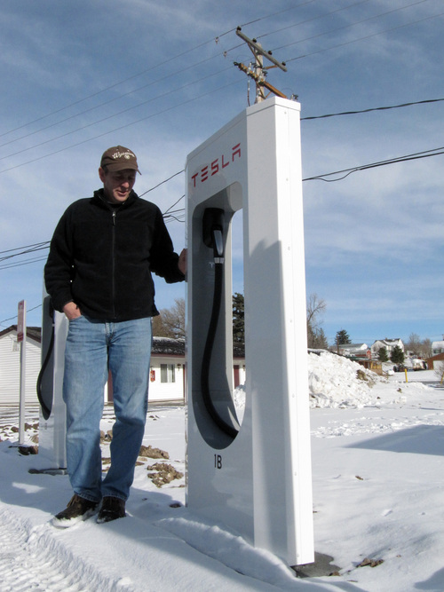 In this Jan. 2, 2014 photo, Mark Kupke, owner of the Covered Wagon Motel in Lusk, Wyo., stands next to one of four Tesla Supercharger units installed in December in the hotel courtyard. A Supercharger can recharge a Tesla's depleted battery pack to a 90-percent level within 45-50 minutes, several times faster than any other charging option for the electric cars. Lusk is on the route of Tesla's first network of coast-to-coast Supercharger stations. The quick-charge stations promise to make cross-country travel by Tesla much quicker and easier. (AP Photo/Mead Gruver)